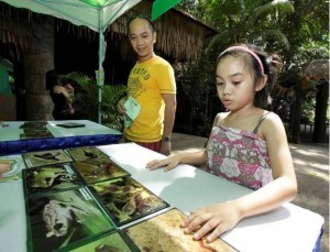 Children at Singapore Zoo learning about the morphological differences of frogs and their tadpoles.