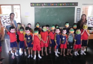 Kindergarten children wearing amphibian masks and holding the South Asian amphibian posters.